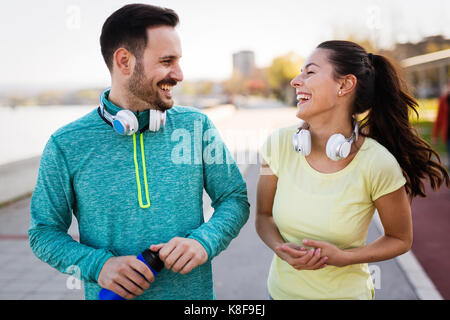 Young attractive couple running outside on sunny day - Stock Photo
