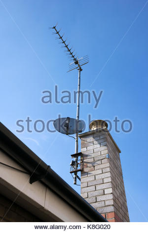 TV aerial and satellite dish fixed to a brick chimney - Stock Photo