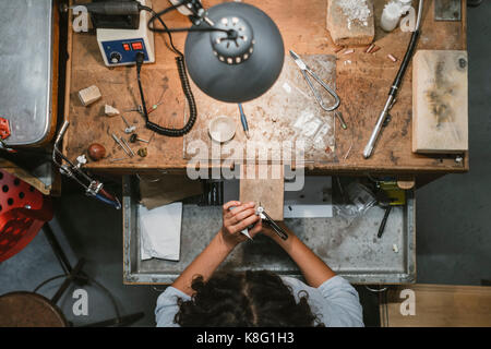 Overhead view of female jeweller using coping saw at workbench - Stock Photo