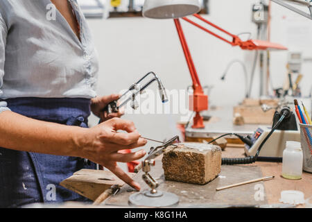 Mid section of female jeweller using blow torch at workbench - Stock Photo