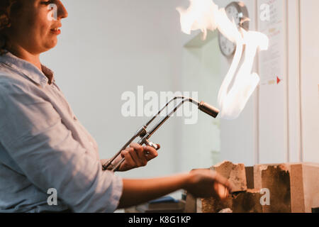 Female jeweller using flaming  blow torch at workbench - Stock Photo