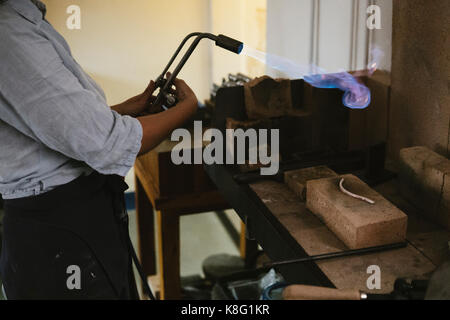 Mid section of female jeweller using flaming  blow torch at workbench - Stock Photo