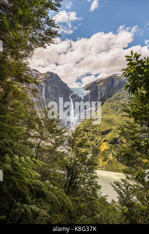 View of waterfall flowing from glacier at edge of  mountain rock face, Queulat National Park, Chile - Stock Photo