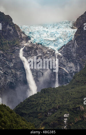 Waterfall flowing from glacier at edge of mountain rock face, Queulat National Park, Chile - Stock Photo