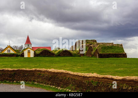 Red rooed church in Glaumbaer village and small cottages with turf roofs in Northern Iceland - Stock Photo