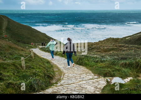 Bedruthan Steps - people walking down the coastal footpath at Bedruthan Steps on the North Cornwall coast. - Stock Photo