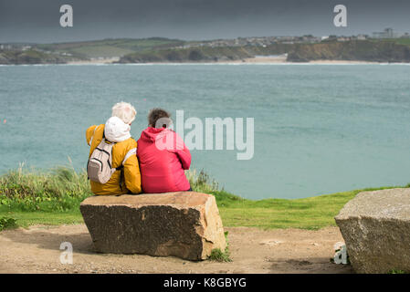 Newquay Cornwall - two walkers sitting on a rock overlooking Newquay Bay at Little Fistral in Newquay, Cornwall - Stock Photo