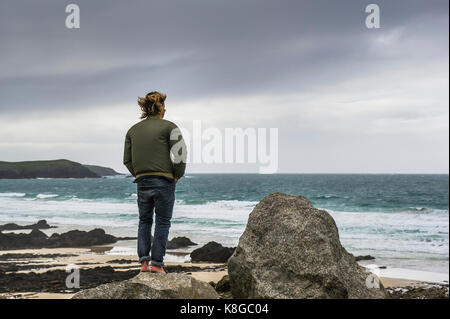 Newquay Cornwall - a barefoot man standing on a rock overlooking Little Fistral in Newquay, Cornwall. - Stock Photo