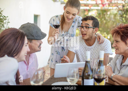 Family having lunch outdoors under grapevine trellis - Stock Photo