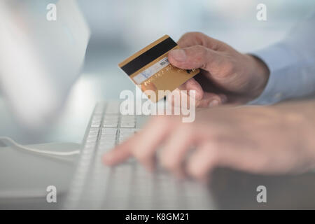 Cropped view of man using keyboard holding credit card - Stock Photo