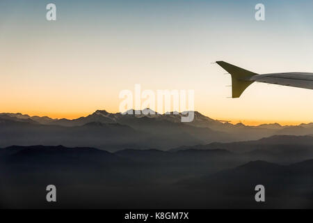 Airplane wing and aerial view of sunset over mountains, Metropolitan Region, Chile - Stock Photo