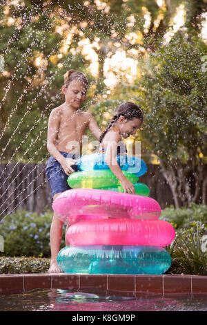 Young girl, standing in the middle of inflatable rings on the side of outdoor swimming pool, brother stacking rings - Stock Photo
