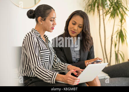 Two businesswomen sitting on office sofa, using laptop, looking at screen - Stock Photo