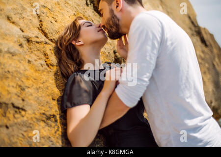 Couple kissing on rock - Stock Photo