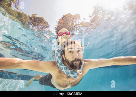 Underwater view of mature man swimming with daughter on piggy back - Stock Photo