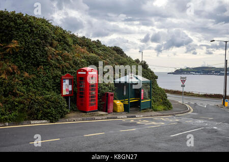 Red phone box and bus stop at Port Jack, Onchan, Isle of Man - Stock Photo