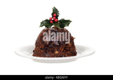 isolated christmas brandy pudding on plate with holly - Stock Photo