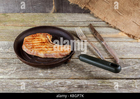 Grilled meat and vegetables on rustic wooden table. savory sauces and salt served with grilled steak on a rustic - Stock Photo