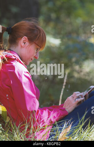 Young woman in pink jacket uses smartphone in the autumn forest - vertical - Stock Photo