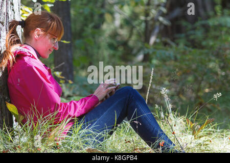 Young woman in pink jacket uses smartphone in the autumn forest - horizontal - Stock Photo