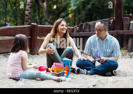 Happy family spending fun time together playing in sand - Stock Photo