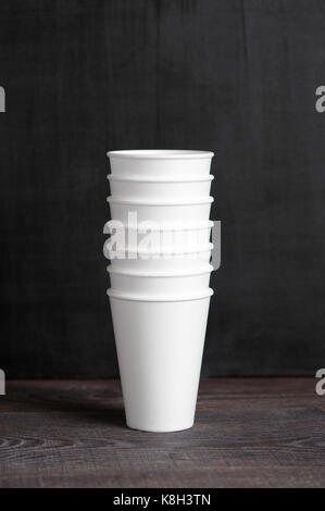 Stack of disposable cups on the dark brown table - Stock Photo