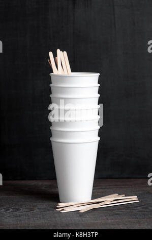 Steck of disposable cups with wooden sticks on the dark brown table - Stock Photo