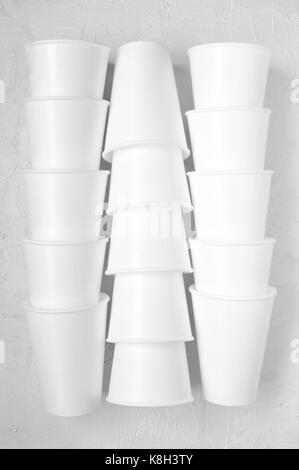 Stacks styrofoam empty cups on the white textured table - Stock Photo