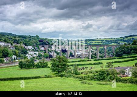 A far reaching landscape view of the great stone arched Calstock Viaduct crossing the Tamar Valley with Calstock - Stock Photo