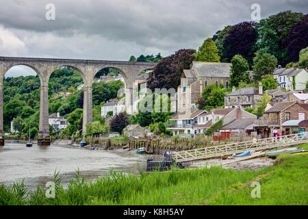 A landscape of the great stone arched Calstock Viaduct crossing the Tamar River going to sea. A green bank of grass - Stock Photo