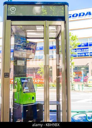 KYOTO, JAPAN - JULY 05, 2017: Public phone in Osaka, Japan. Blurry phone through the glass - Stock Photo