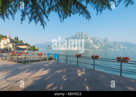 View from the lakeside at central square in medieval Riva di Solto on mountains in the evening sun at Lake Iseo, - Stock Photo