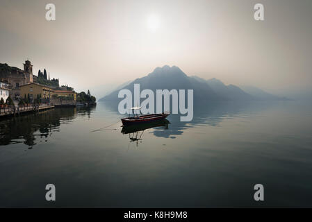Panorama of a small boat on calm Lake Iseo in front of hazy mountains and Riva di Solto lakeside promenade in the - Stock Photo