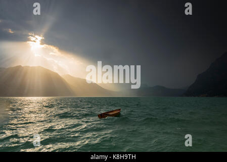 Thunderstorm raging on Lake Iseo with sun bursting through clouds and abandoned boat bopping up and down in the - Stock Photo