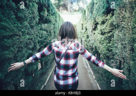 Young woman walking in the park labyrinth in Barcelona - Stock Photo