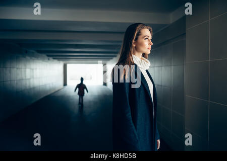 Beautiful lonely woman in a subway tunnel with frighten silhouette on background. surrealism concept - Stock Photo