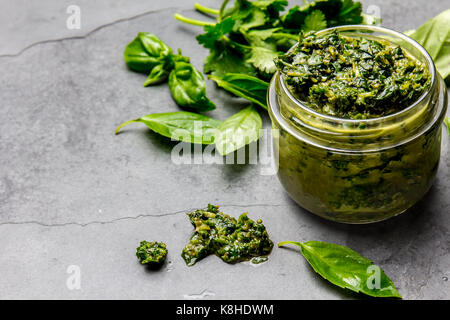 Chimichurri sauce. Argentine green parsley basil sauce chimichurri for barbecue asado in glass jar, gray slate background. - Stock Photo