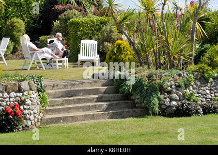 an older or middle aged couple relaxing in the summer sunshine in a beautifully landscaped garden at a hotel on - Stock Photo
