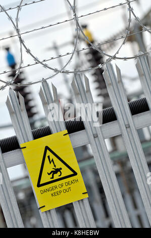 an electricity board sub station with palisade fencing and danger, danger of death yellow signs attached to the - Stock Photo