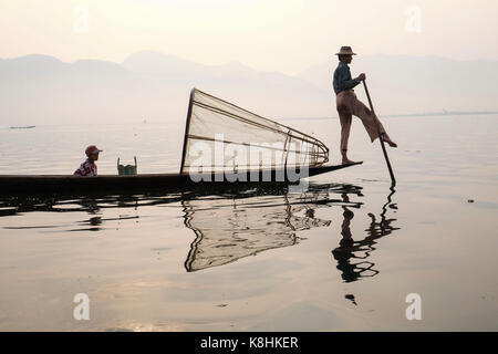 Burma, Myanmar: fisherman on a barge on Inle Lake. Fisherman with his son on a barge and cone-shaped fish trap - Stock Photo