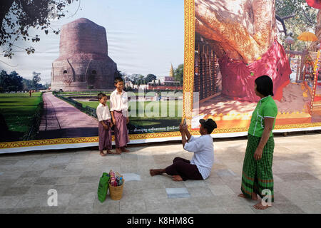 Burma, Myanmar: Burmese tourists taking pictures of each other in front of giant posters in Rangoon. - Stock Photo