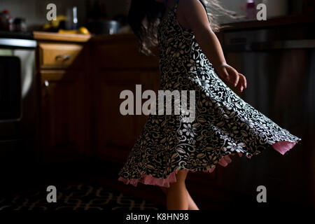Midsection of girl spinning around at home in darkroom - Stock Photo
