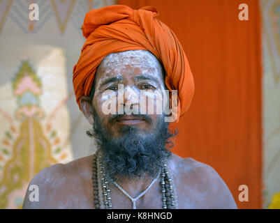 Young Indian Hindu sadhu with orange turban and sacred white ash (vibhuti) all over his face and beard - Stock Photo