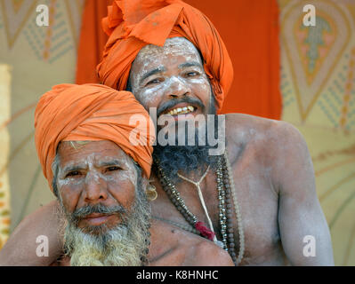 Two happy Indian Hindu sadhus with orange turbans and sacred white ash all over their faces, beards and bodies, - Stock Photo