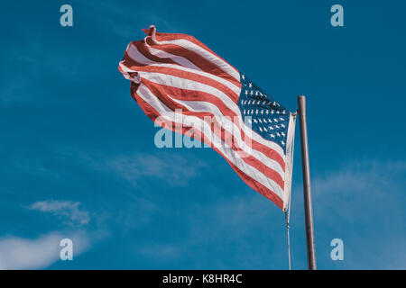 Low angle view of American Flag against blue sky - Stock Photo