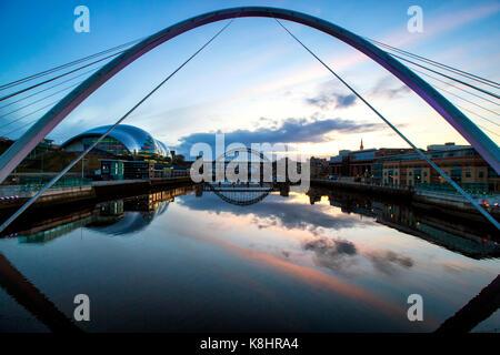 Gateshead Millennium Bridge over river against sky - Stock Photo