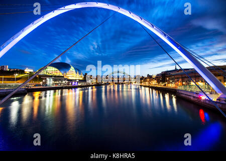 Illuminated Gateshead Millennium Bridge over river against sky - Stock Photo