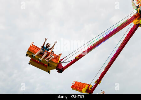 Low angle view of father and son enjoying in chain swing ride against sky - Stock Photo