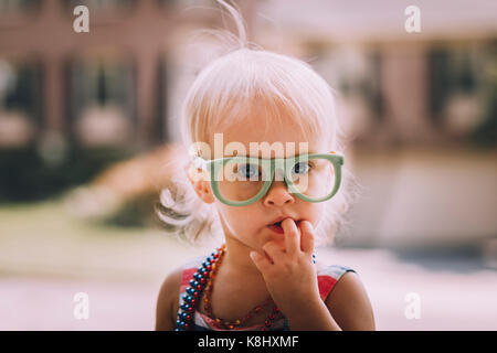 Portrait of cute baby girl wearing eyeglasses with finger in mouth - Stock Photo