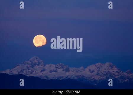 Full moon setting over Mount Triglav, the highest mountain in the Julian Alps at dawn in Slovenia. - Stock Photo